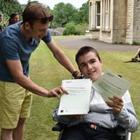 Callum helping student hold awards