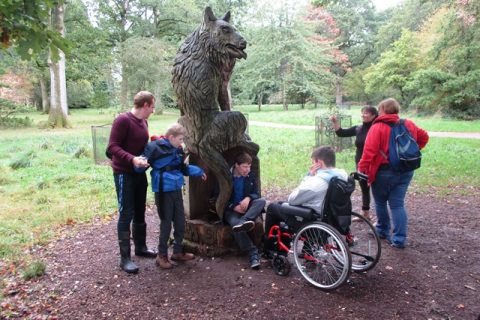 Class looking at wooden wolf statue